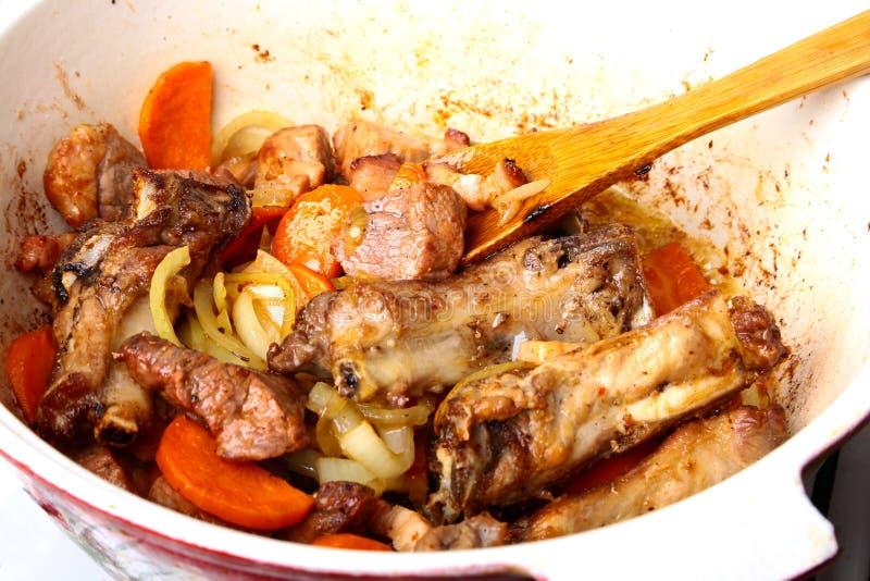 Roheisenplatte mit der geschnittenen gegrillten Rippe, die ein mittleres Steak mit gebratener Kartoffel und Gewürzen kocht stockbild