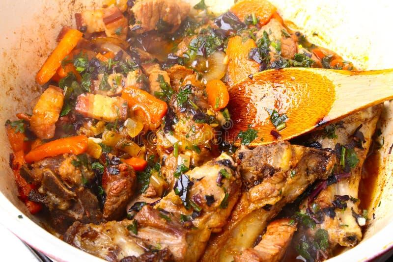 Roheisenplatte mit der geschnittenen gegrillten Rippe, die ein mittleres Steak mit gebratener Kartoffel und Gewürzen kocht lizenzfreie stockfotos