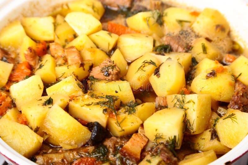 Roheisenplatte mit der geschnittenen gegrillten Rippe, die ein mittleres Steak mit gebratener Kartoffel und Gewürzen kocht lizenzfreies stockfoto