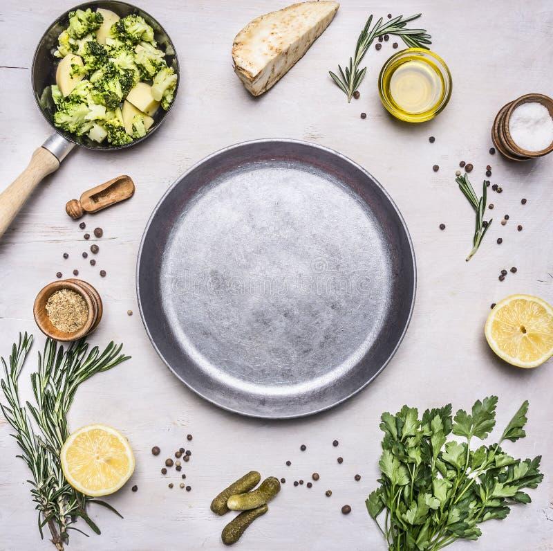Roher Brokkoli in einer kleinen Bratpfanne, Petersilie, Öl, Salz, Zitrone, Essiggurken ausgebreitet um einen Wannenplatz für Text lizenzfreie stockfotos