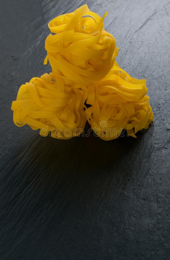 Roher gelber italienischer Teigwarenfettuccine, -fettuccelle oder -Bandnudeln stockfotografie