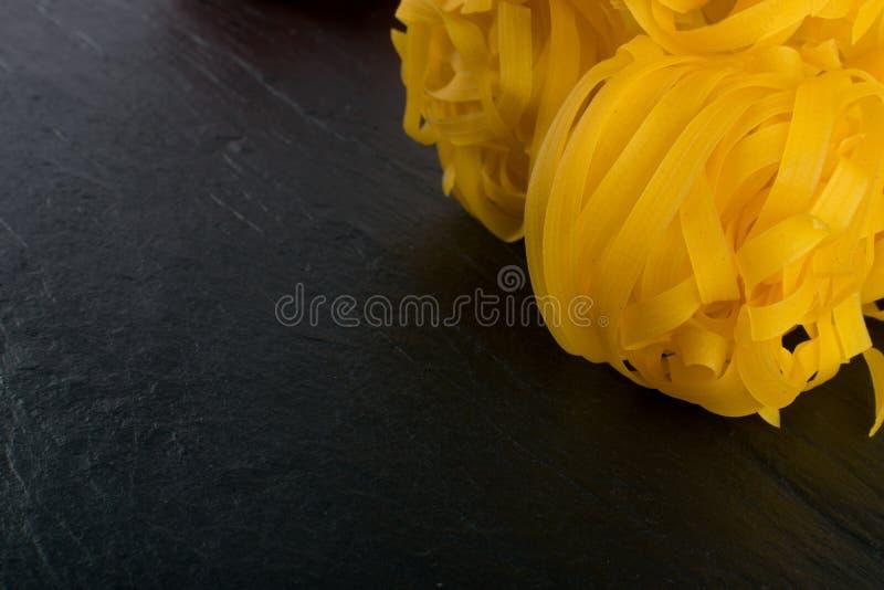 Roher gelber italienischer Teigwarenfettuccine, -fettuccelle oder -Bandnudeln stockfoto