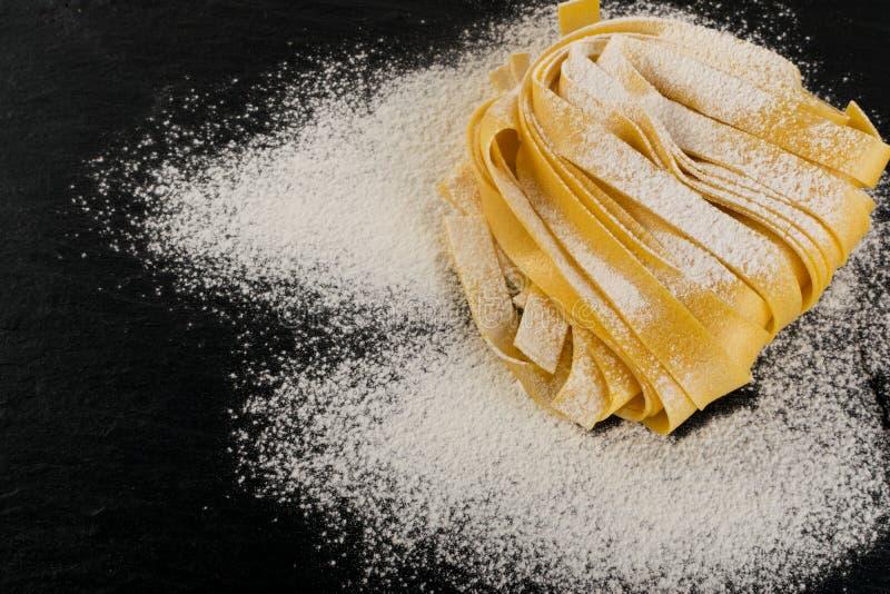 Roher gelber italienischer Teigwarenfettuccine, -fettuccelle oder -Bandnudeln stockfotos