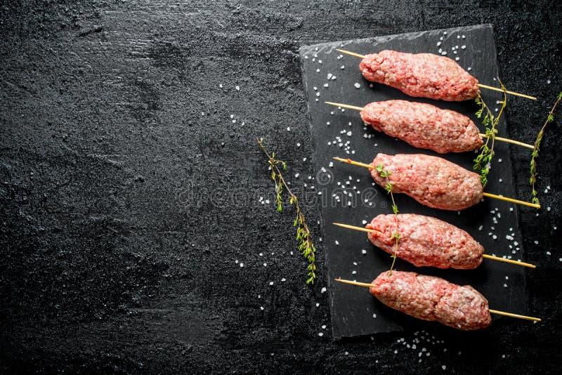 Roher Kebab des Rinderhackfleischs mit Thymian und St?cken Salz lizenzfreies stockfoto