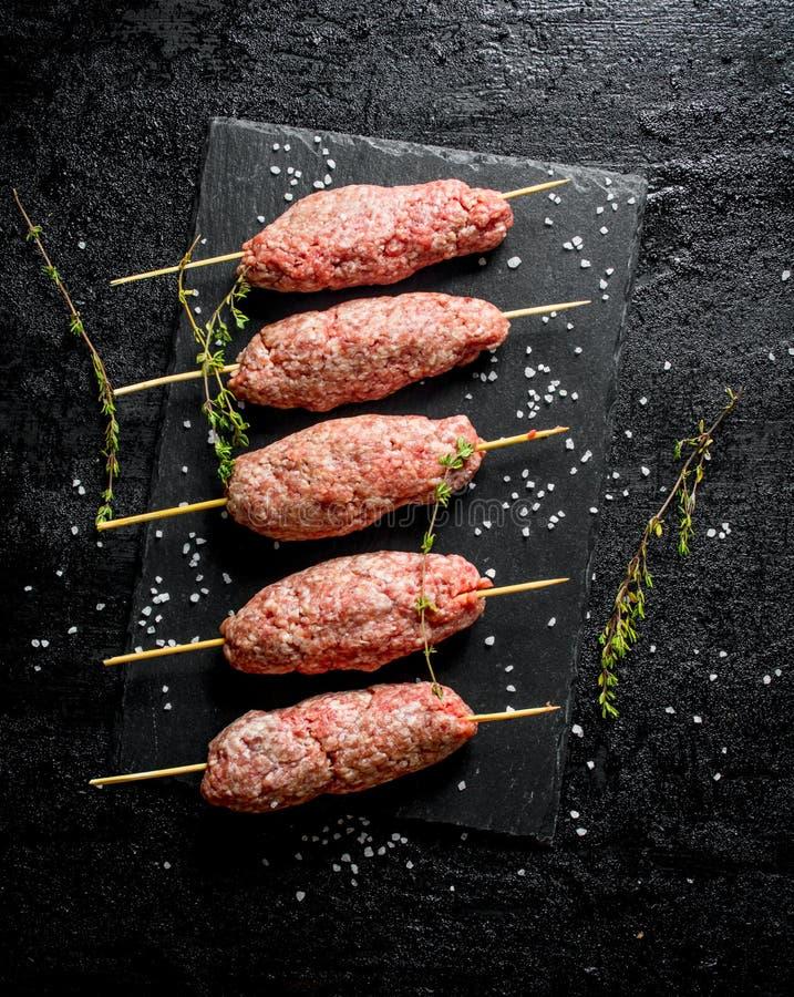 Roher Kebab des Rinderhackfleischs mit Thymian und St?cken Salz stockbild