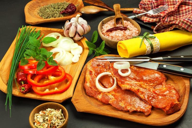Roher marinierter Schweinefleischhals Vorbereitung des Fleisches für das Grillen Rohes Schweinefleisch und Gewürze Frischfleisch  lizenzfreie stockfotos