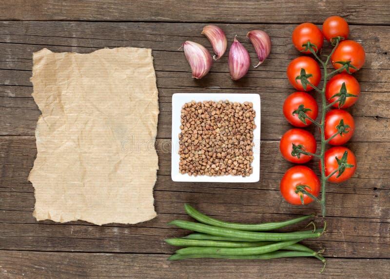 Roher organischer Buchweizen, Gemüse und Papier stockfotografie