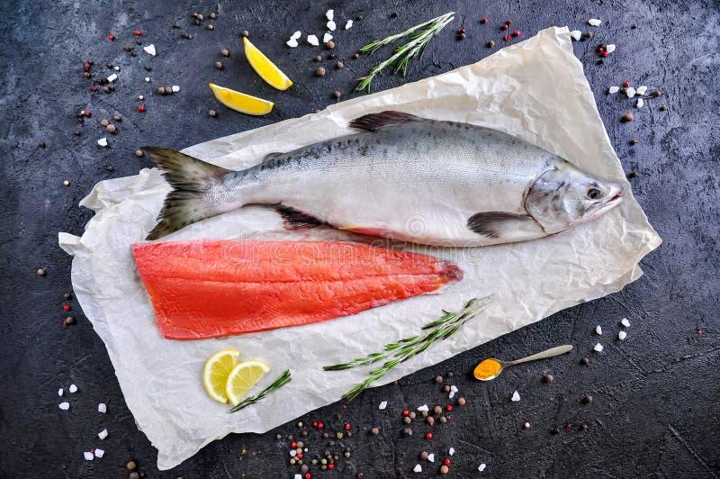 Roher Salmon Fish mit Gew?rzen auf schwarzem Steinhintergrund Draufsichtebenenlage stockfotos