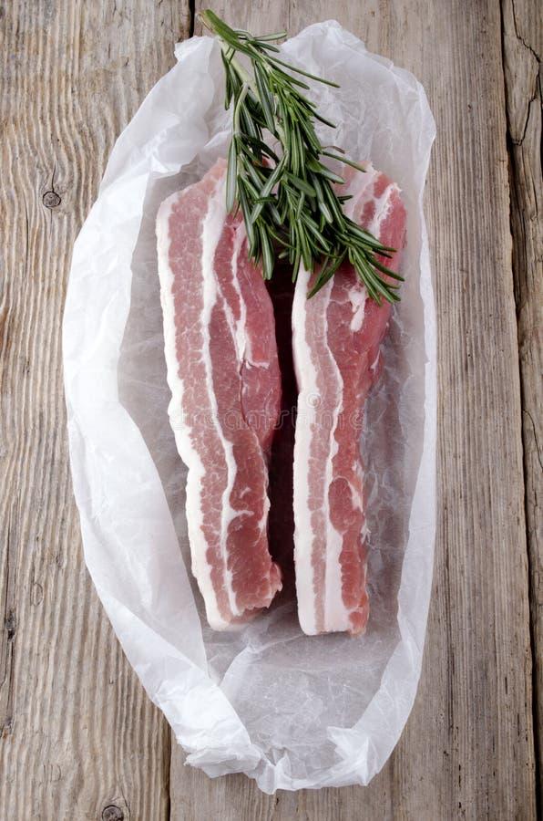Roher Schweinebauch mit Rosmarin lizenzfreies stockbild