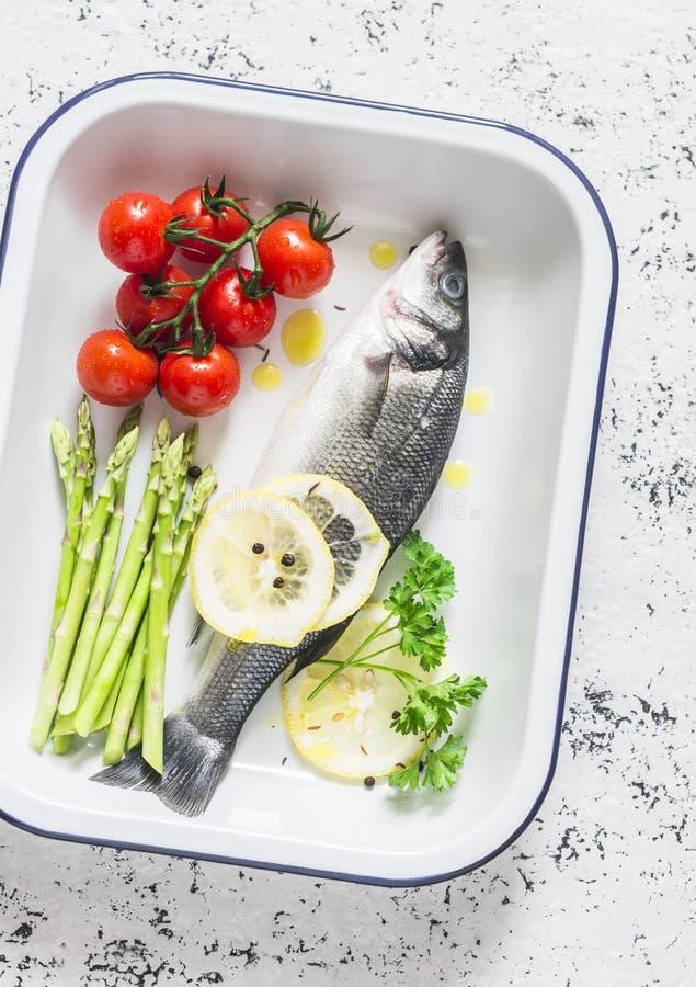 Roher Wolfsbarsch, Kirschtomaten und Spargel im Backblech Bestandteile für das Mittagessen Auf einem hellen Hintergrund lizenzfreies stockfoto