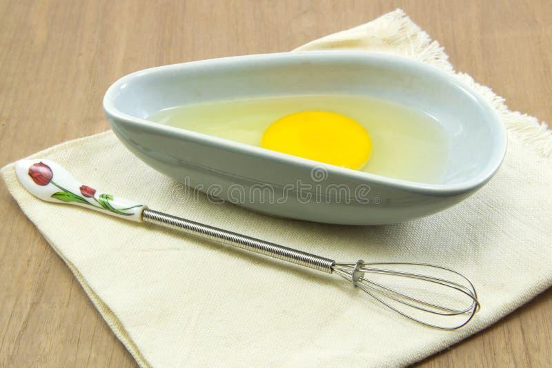 Rohes Ei in der Schüssel mit wischen auf hölzerner Tabelle lizenzfreies stockbild
