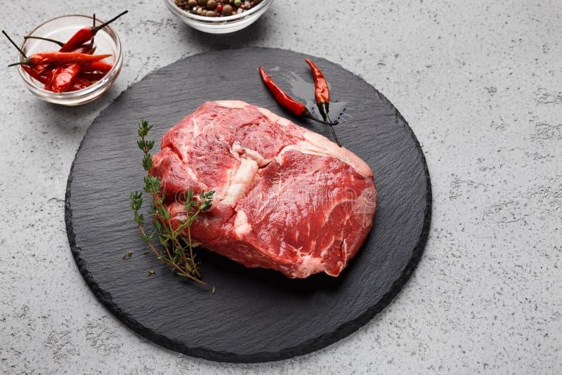 Rohes Fleisch auf dem schwarzen Brett bereit zum Kochen stockbild