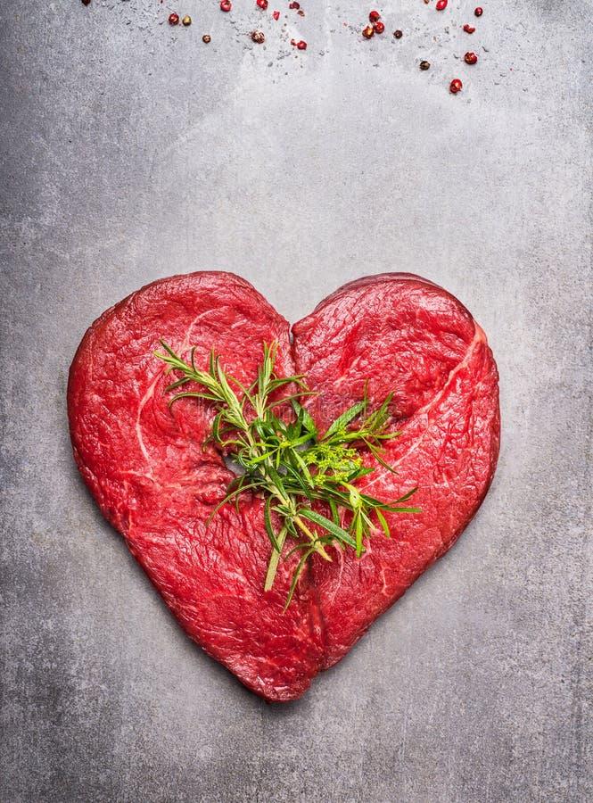 Rohes Fleisch der Herzform mit Kräutern und Text auf grauem konkretem Hintergrund stockfoto