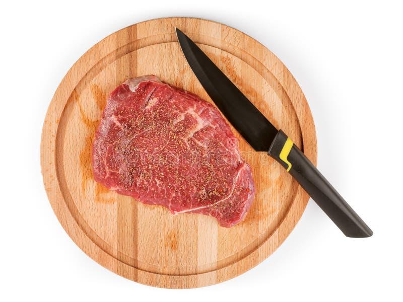 Rohes Fleisch für Steak und Küchenmesser auf rundem Schneidebrettisolator lizenzfreie stockbilder