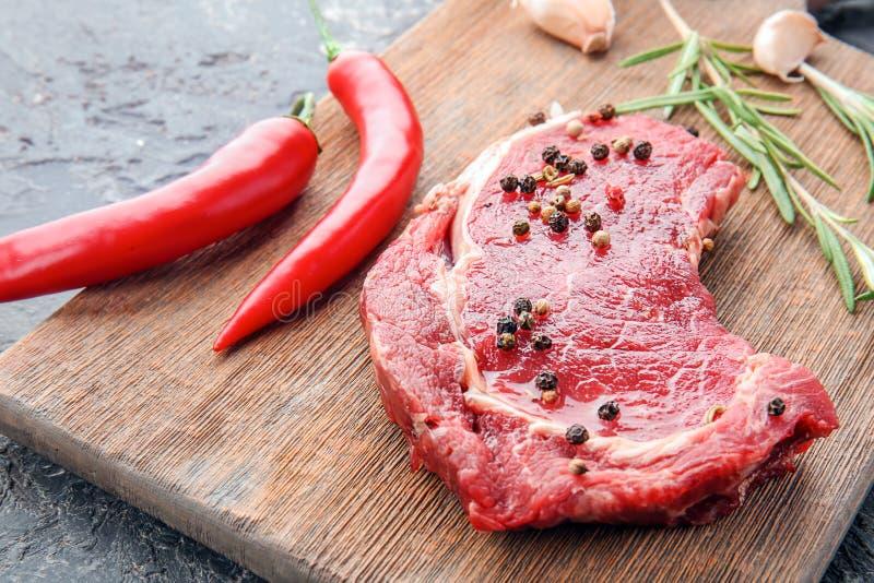Rohes Fleisch mit Gewürzen auf hölzernem Brett, Nahaufnahme lizenzfreie stockbilder