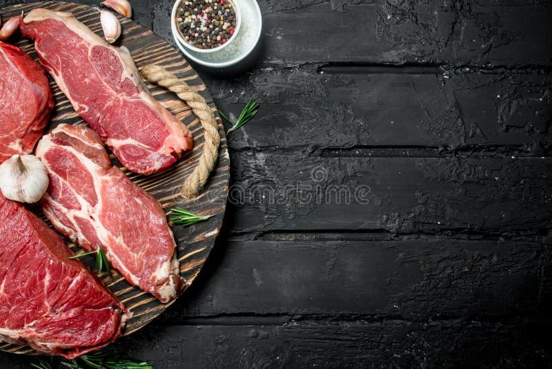 Rohes Fleisch Schweinefleisch- und Rindfleischsteaks auf einem Behälter mit Gewürzen und Rosmarinzweig stockbilder