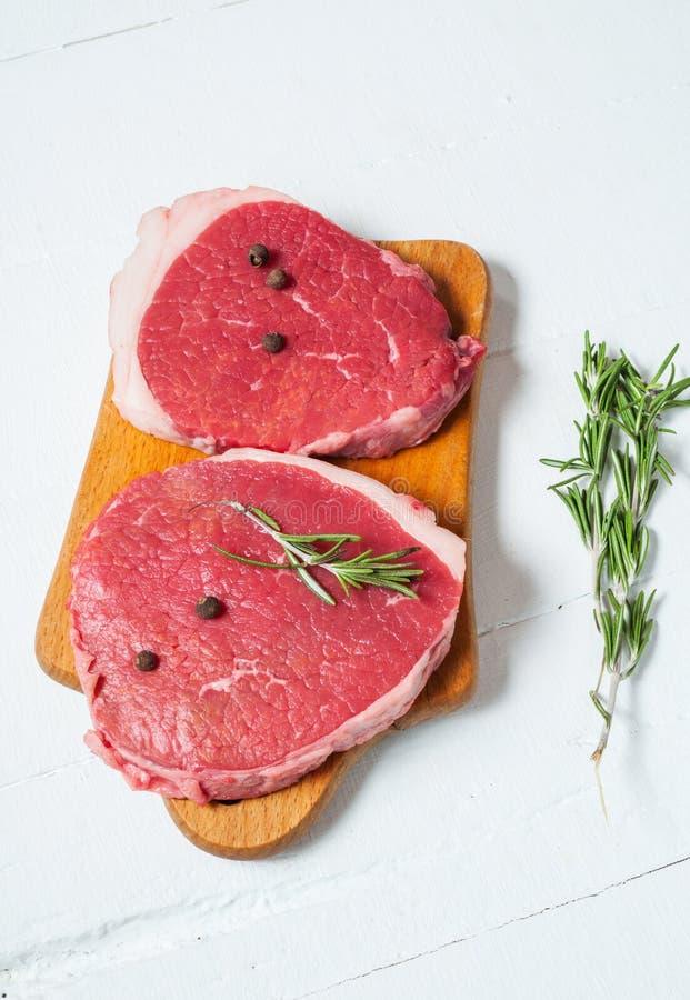 Rohes Fleisch und Rosmarin auf weißem hölzernem Brett Frisches Rindfleisch Bereiten Sie zur Röstung vor stockfotos