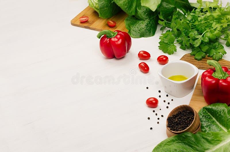 Rohes frisches grünes Gemüse, Grüns, rote Kirschtomaten und Küchengeschirr auf weichem weißem hölzernem Brett, Grenze stockfotos