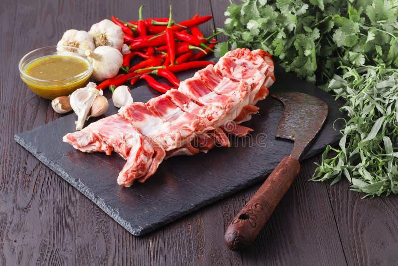 Rohes frisches Lammfleisch mit Gewürzen auf hölzernem Hintergrund lizenzfreie stockfotos