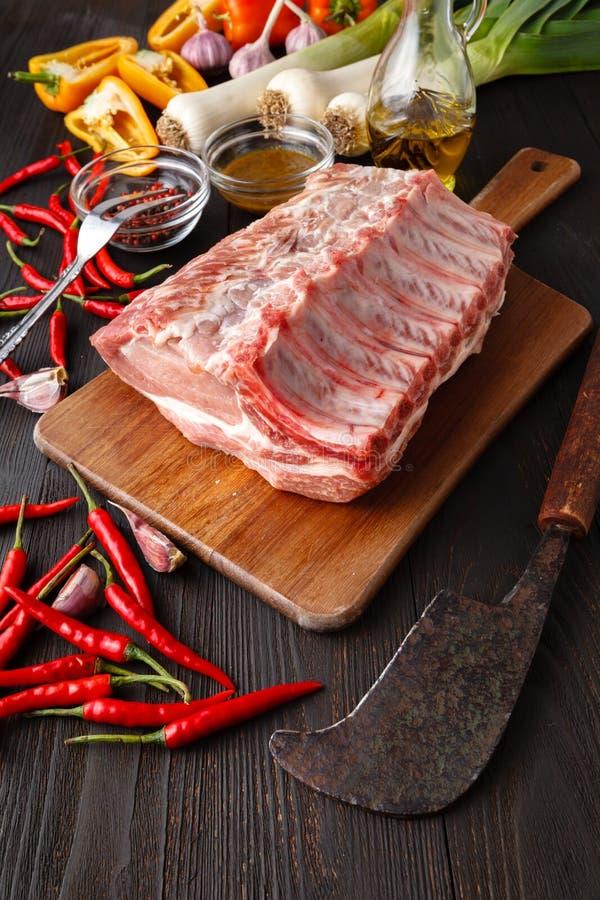 Rohes Frischfleisch Kalbfleischrippe Steak auf Knochen und Gewürze auf dunklem BAC lizenzfreies stockfoto