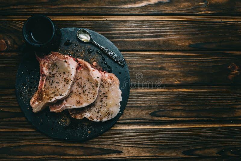 Rohes Frischfleisch Schweinefleischsteak und -gewürze auf dunklem hölzernem Hintergrundbrettschiefer mit Honigmesser stockbild
