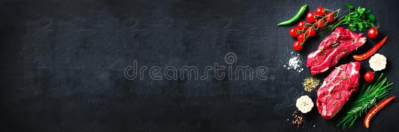 Rohes Frischfleischsteak mit Kirschtomaten, Peperoni, Knoblauch, Öl und Kräutern auf dunklem Stein, konkreter Hintergrund fahne stockfoto