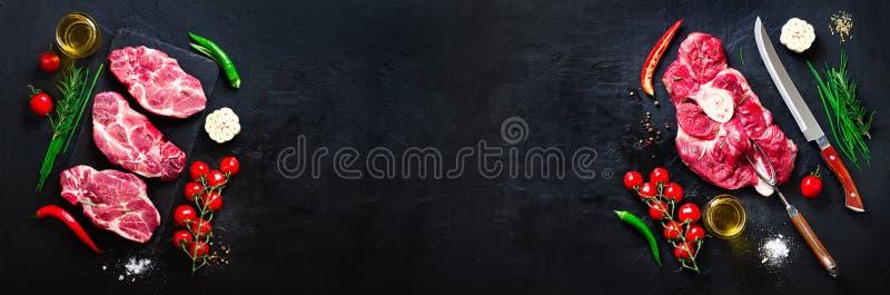 Rohes Frischfleischsteak mit Kirschtomaten, Peperoni, Knoblauch, Öl und Kräutern auf dunklem Stein, konkreter Hintergrund fahne lizenzfreies stockfoto