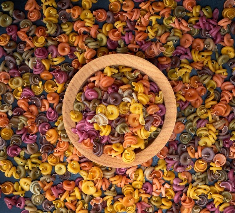 Rohes fusilli Teigwaren der mehrfarbigen Spirale in einer hölzernen Schüssel stockfotografie