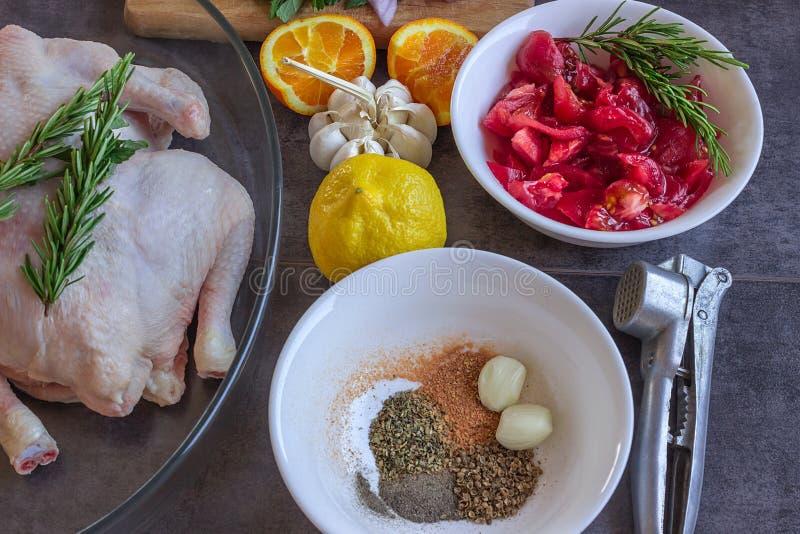 Rohes ganzes Huhn mit geschnittenen Tomaten, Knoblauch, Zitrone und Orange lizenzfreie stockfotos
