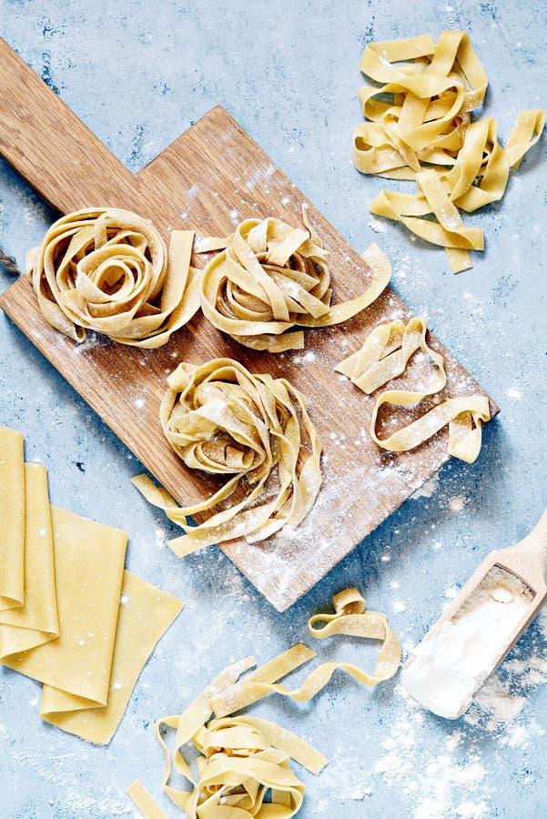 Rohes gelbes italienisches Teigwarenpappardelle, -Fettuccine oder -Bandnudeln auf einem blauen Hintergrund, Abschluss oben stockfotos