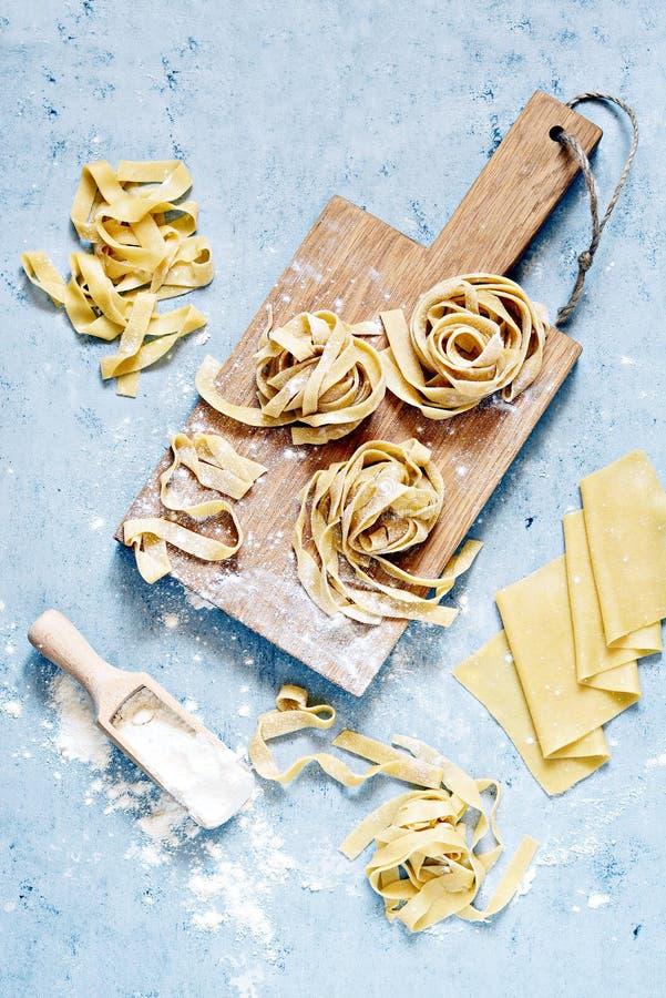 Rohes gelbes italienisches Teigwarenpappardelle, -Fettuccine oder -Bandnudeln auf einem blauen Hintergrund, Abschluss oben stockfoto