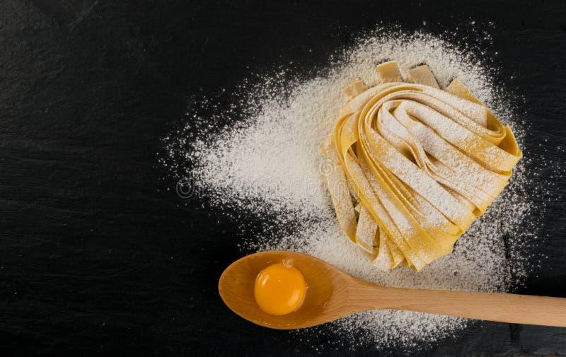 Rohes gelbes italienisches Teigwarenpappardelle, -Fettuccine oder -Bandnudeln stockbilder