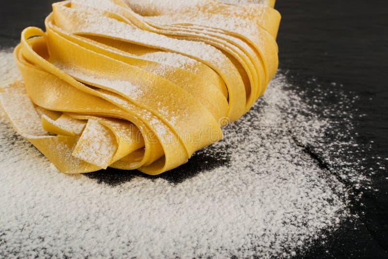 Rohes gelbes italienisches Teigwarenpappardelle, -Fettuccine oder -Bandnudeln stockfotos