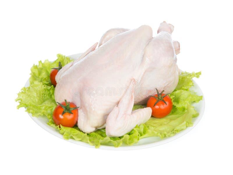 Rohes grobes Huhn auf einer Platte geschmückt mit Gemüse stockbild