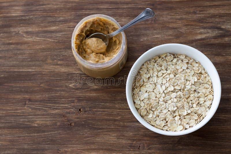 Rohes Hafermehl in einer wei?en Sch?ssel mit Erdnussbutter, Bestandteile zum ein k?stliches gesundes Fr?hst?ck auf einem h?lzerne stockbilder