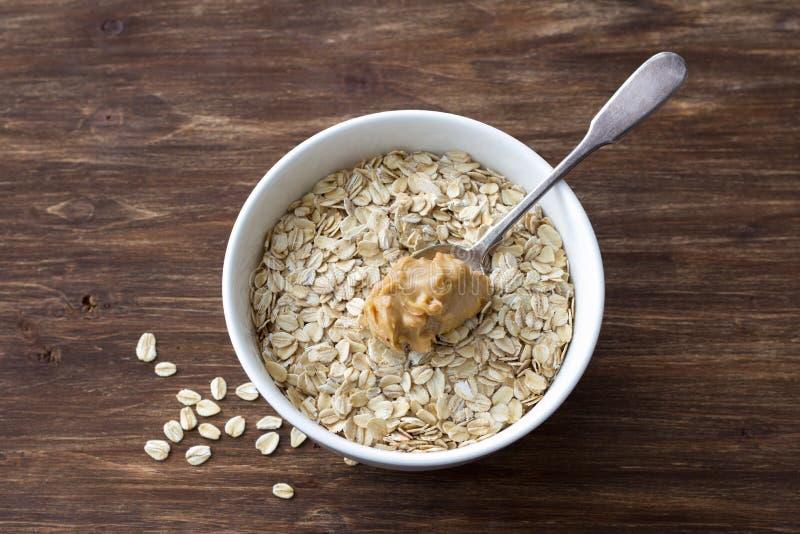 Rohes Hafermehl in einer wei?en Sch?ssel mit Erdnussbutter, Bestandteile zum ein k?stliches gesundes Fr?hst?ck auf einem h?lzerne stockfoto