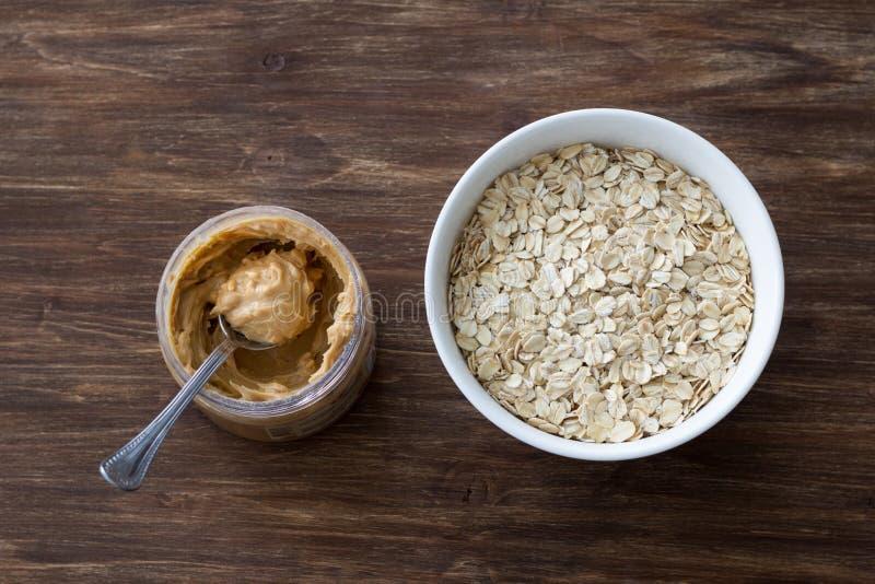 Rohes Hafermehl in einer wei?en Sch?ssel mit Erdnussbutter, Bestandteile zum ein k?stliches gesundes Fr?hst?ck auf einem h?lzerne stockfotografie