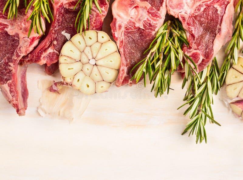 Rohes Lammfleisch mit Knoblauch und Rosmarin auf weißem hölzernem backgound, Draufsicht lizenzfreie stockfotos
