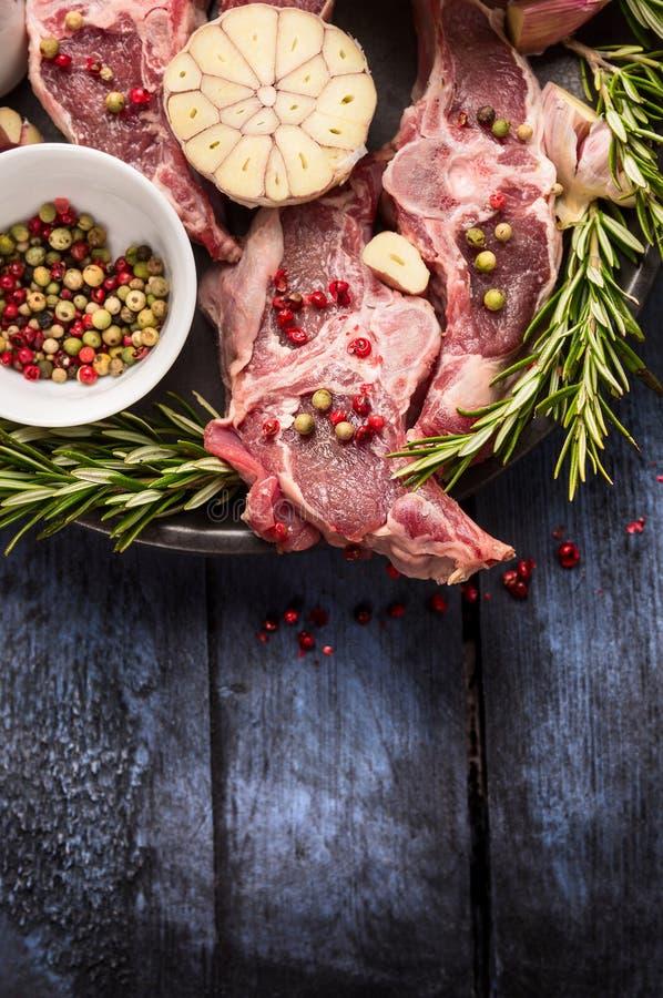 Rohes Lammfleisch mit Pfefferkorn, Rosmarin und Knoblauch auf blauem rustikalem Holztisch stockfoto