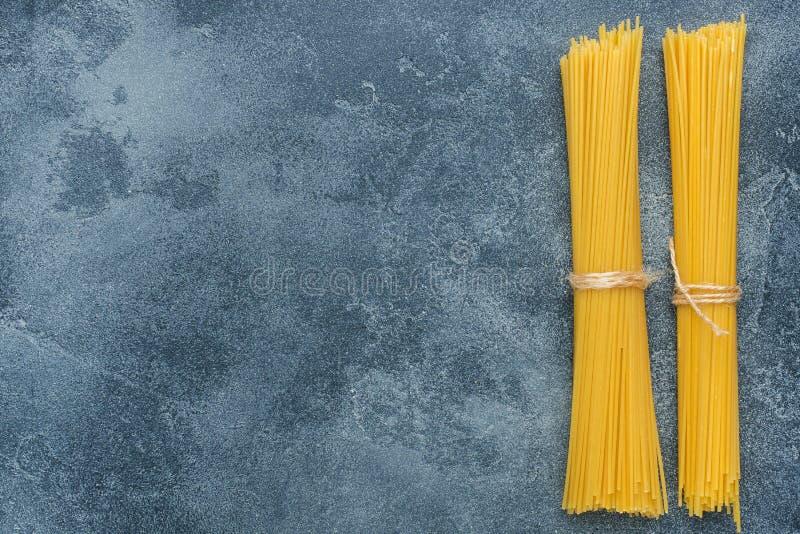 Rohes Makkaroni, Spaghettis auf einer dunklen Steintabelle mit Kopienraum Selbst gemachte italienische Teigwaren lizenzfreies stockbild