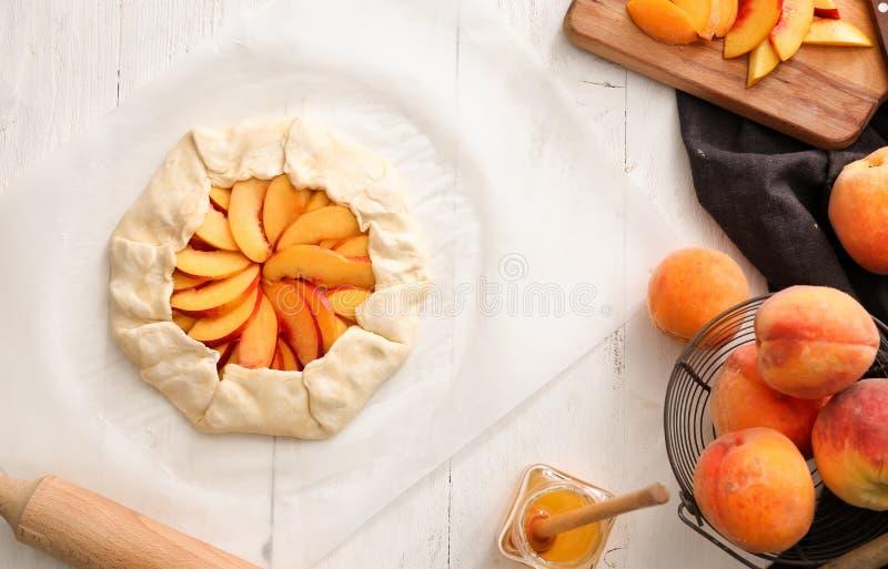 Rohes Pfirsich galette mit frischer Frucht auf Tabelle stockbilder