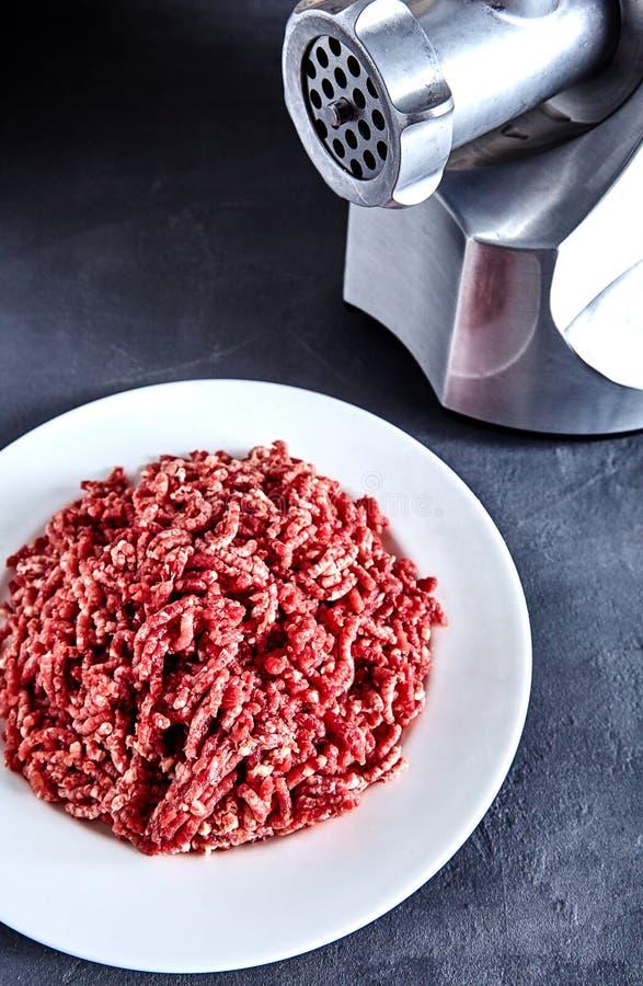 Rohes Rinderhackfleisch auf einer weißen Platte mit Fleischwolf lizenzfreie stockbilder