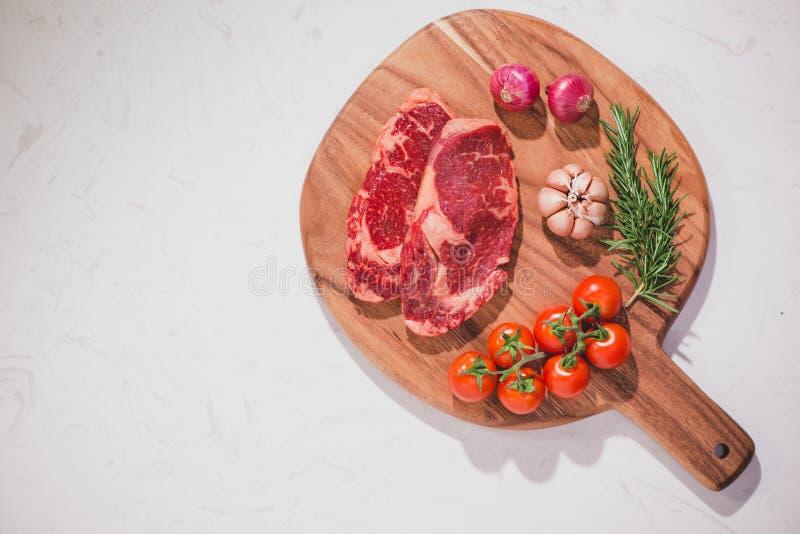 Rohes Rindfleisch auf einem Schneidebrett mit Gewürzen und Bestandteilen für Gurren stockfotografie