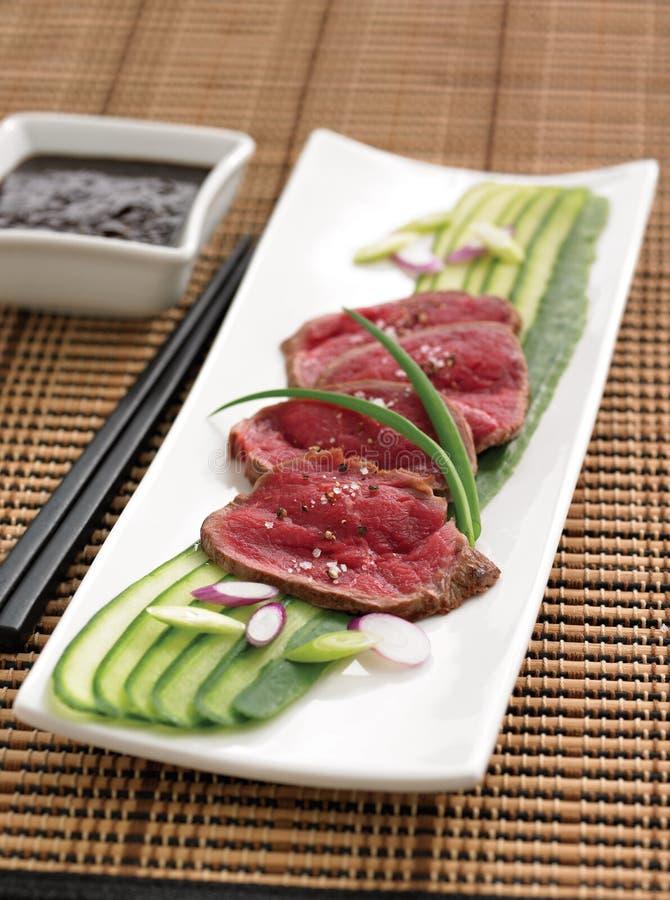 Rohes Rindfleisch auf Gurkenscheiben lizenzfreie stockbilder