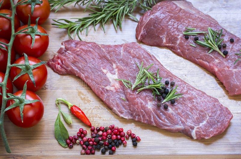 Rohes Rindfleischfleisch auf einem dunklen hölzernen Brett stockbilder