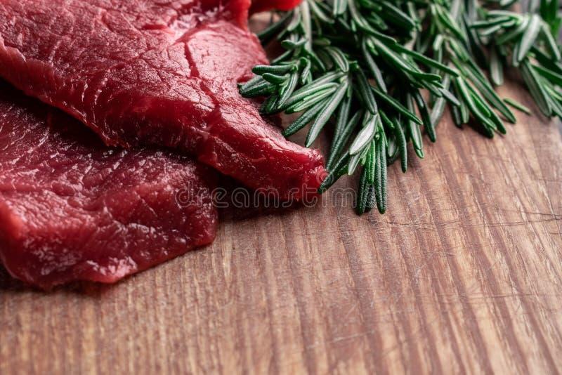 Rohes Rindfleischsteak mit frischem Rosmarin auf einem hölzernen Brett mit Raum für Text stockfotos