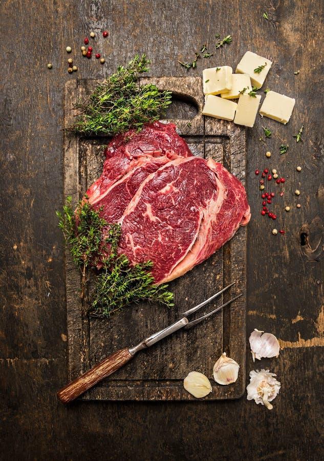 Rohes Rindfleischsteak mit Thymian, Butter und Fleisch gabelt auf dunklem rustikalem Schneidebrett lizenzfreies stockbild