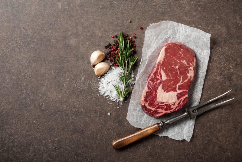 Rohes Rippenaugensteak, Gewürze und Weinlesefleisch gabelt auf Steintabelle lizenzfreies stockbild