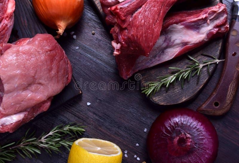 Rohes Schweinefleisch- und Rindfleischfleisch und Rippen auf den dunklen Brettern umgeben durch Zwiebel, Rosmarin und Gewürze lizenzfreies stockfoto