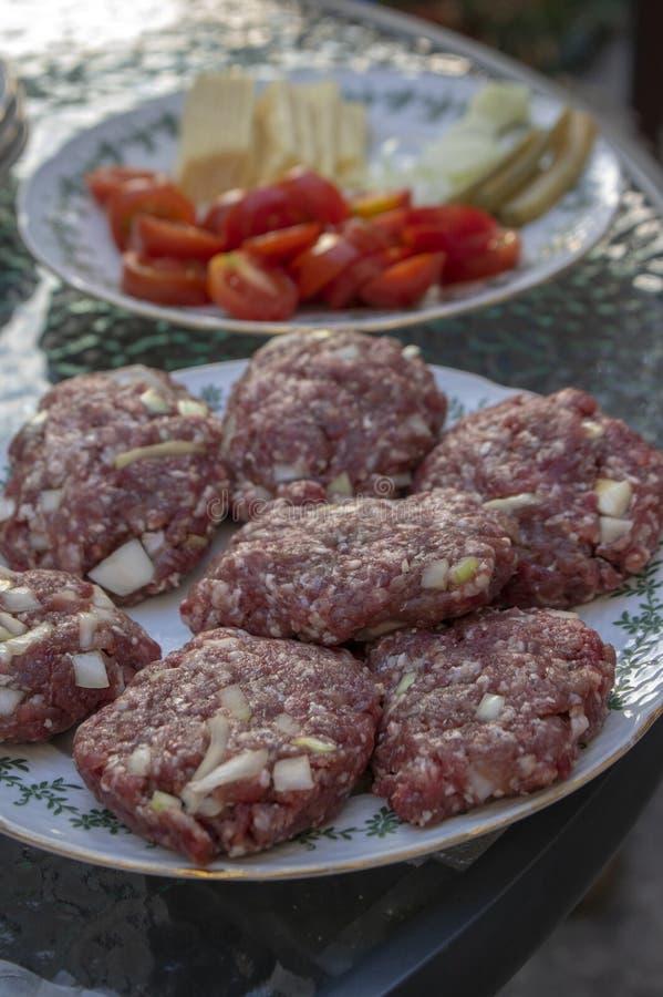Rohes Schweinefleisch- und Rindfleischfleisch zugebereitet für Hamburger auf weißem gerundetem Schneidebrett stockfoto